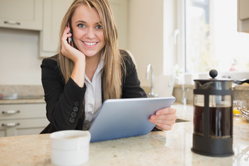 Smiling woman with tablet and mobile phone