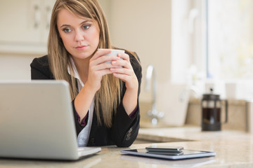 Concentrated woman looking at laptop with coffee in hand