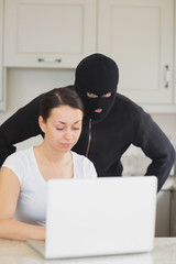 Burglar looking at the laptop behind  woman