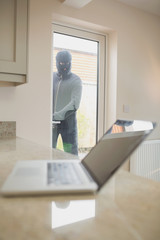 Burglar looking at laptop through the window