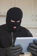 Suspicious burgler holding tablet pc