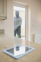 Burglar looking at tablet pc through kitchen door