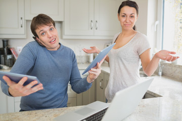 Busy man using two tablets and laptop with wife holding hands up