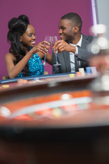 Couple sitting clinking glasses at the roulette table