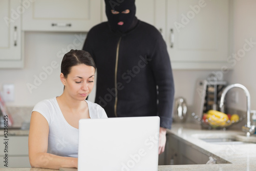 Woman typing on the laptop while  burglar looking at it