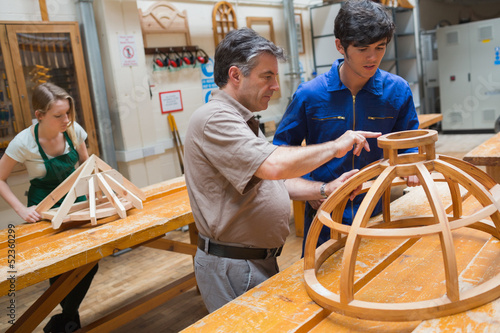Teacher helping a student in a woodwork class