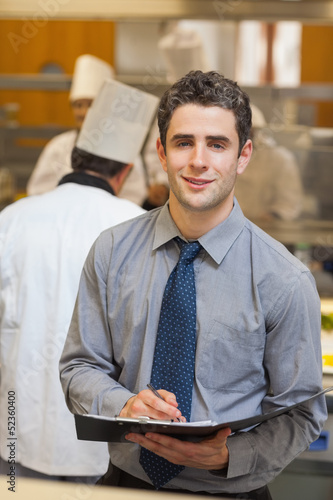 Smiling waiter writing in folder