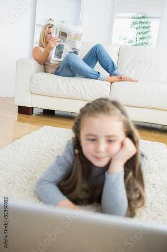 Girl working with laptop with her mother reading the newspaper