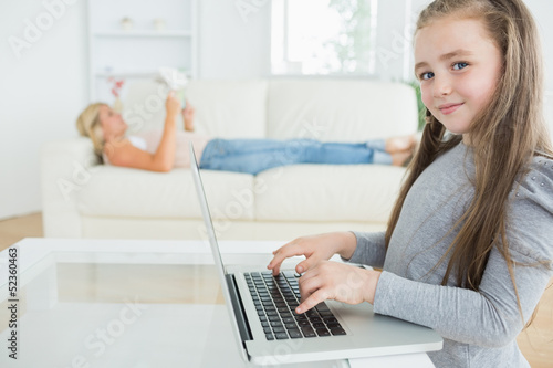 Girl working on laptop and her mother reading the newspaper