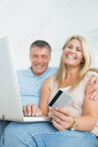 Couple sitting on sofa shopping online