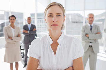 Serious businesswoman standing with arms folded