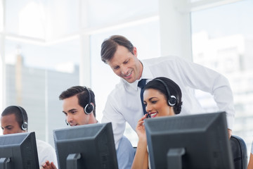 Manager listening to call centre employee