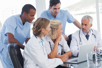 Smiling medical team using laptop