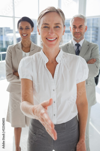 Smiling businesswoman giving a handshake with colleagues behind