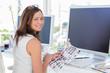 Editor looking over shoulder at camera at her desk