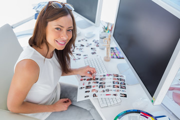 Smiling designer holding contact sheet