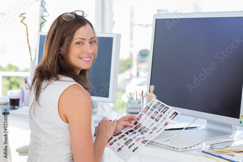 Editor looking over shoulder at camera at her desk