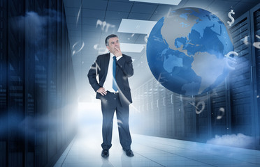 Businessman standing in data center with currency graphics and e
