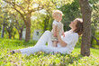 beautiful young mother and osn  relaxing sitting grass backgroun
