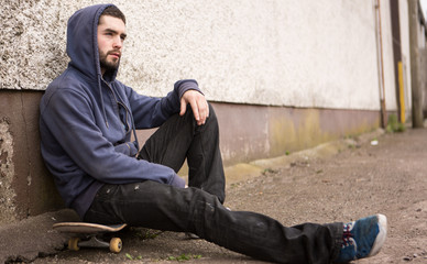 Skater sitting on his board looking thoughtful
