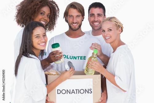 Happy volunteers putting food in donation box