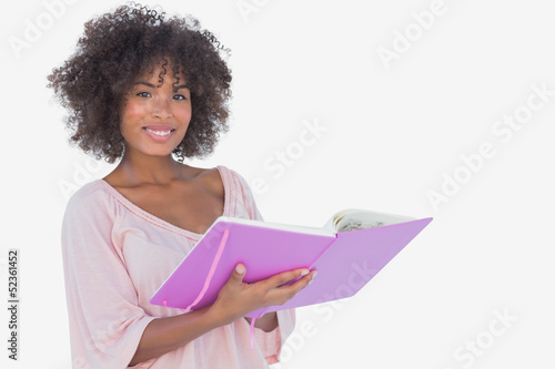 Beautiful woman holding photo album and smiling at camera