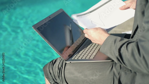 Closeup of businessman working with notebook and papers