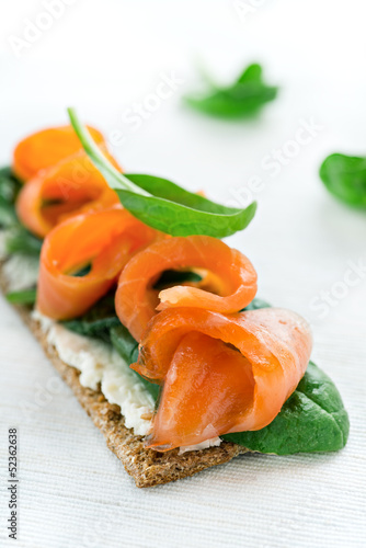 Salted salmon on crispy bread with cheese and spinach