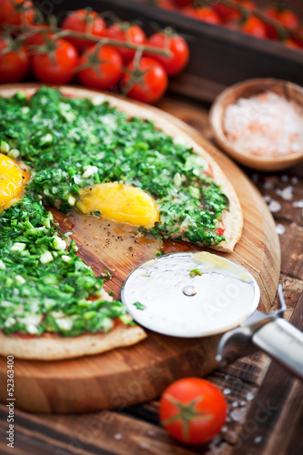 Pizza from oat bran with spinach, green onions and eggs
