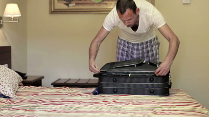 Young man unpacking his case in hotel