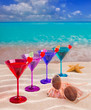 colorful cocktail in a row with cherry on tropical sand beach