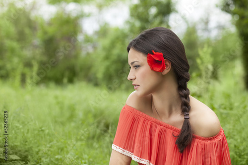 portrait of a beautiful lonely girl with a flower in her hair