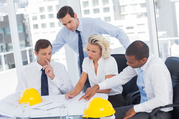 Four architects working on blueprints