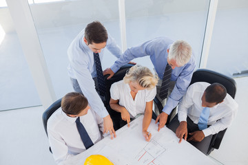 Five architects working on blueprints