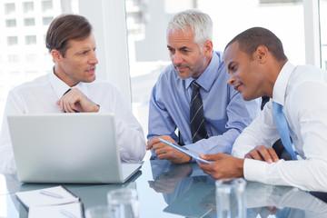 Three businessmen watching a laptop