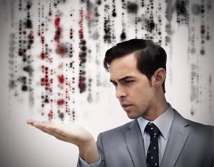 Handsome businessman holding hand out over matrix