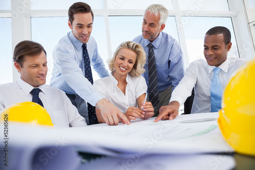 Business people laughing and working on construction plan