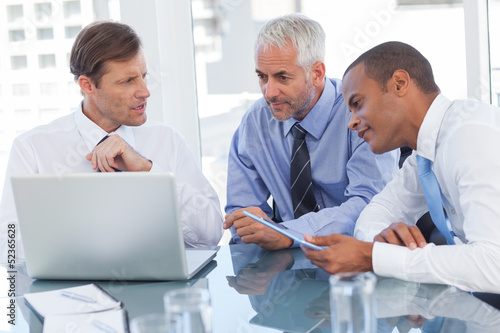 Three businessmen watching a laptop