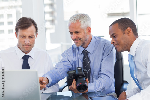 Businessman holding a camera and pointing at the laptop