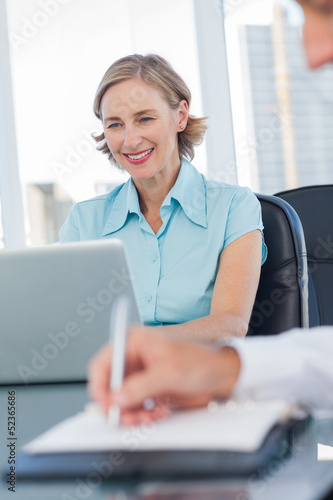 Smiling businesswoman using her laptop
