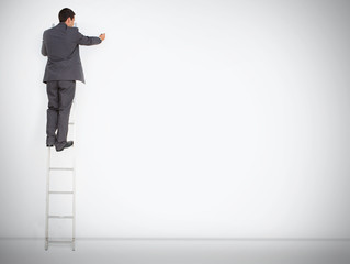 Businessman standing on ladder drawing on large copy space