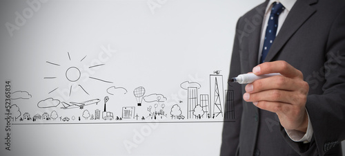 Businessman drawing out a town plan doodle