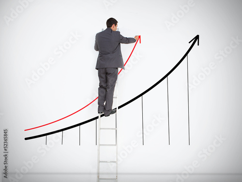 Businessman standing on ladder drawing graph