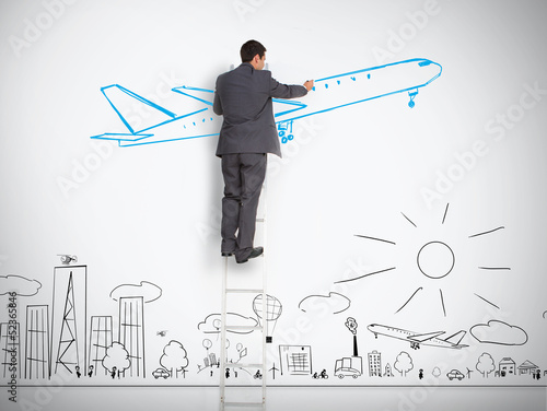 Businessman standing on ladder drawing airplane above town
