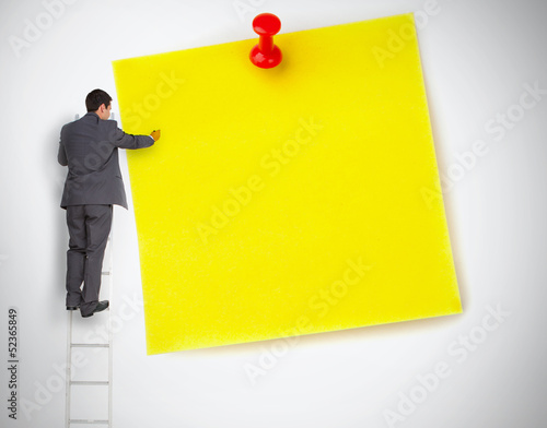 Businessman standing on ladder writing on large yellow note