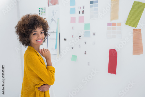 Cute designer standing in front of material samples