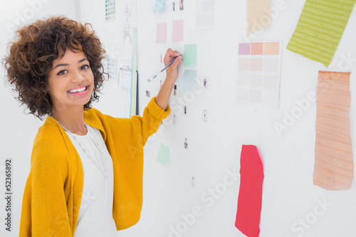 Beautiful designer standing in front of material samples