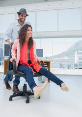 Creative business colleagues having fun on the office chair