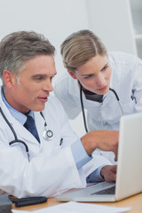 Concentrated doctor pointing at a laptop