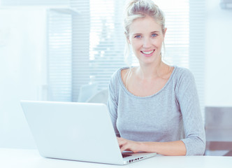 Smiling woman using her laptop